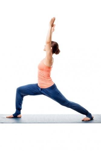 Beautiful sporty fit yogini woman practices yoga asana Virabhadrasana 1 - warrior pose 1 isolated