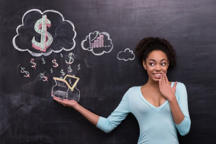 Photo of young afro-american woman on chalkboard background. Woman smiling and cheerfully looking at dollar signs and purse painted on chalkboard