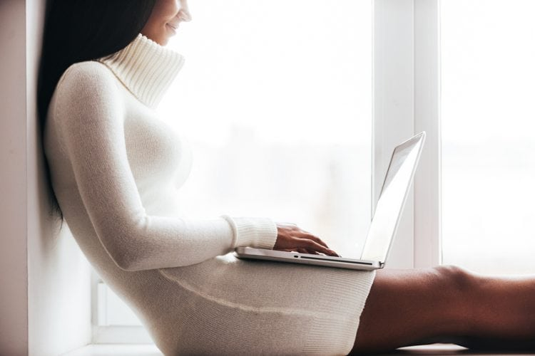 Cropped image of attractive young African woman in warm sweater working on laptop while sitting on the window sill
