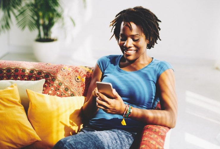 black woman in couch talking to men on mobile