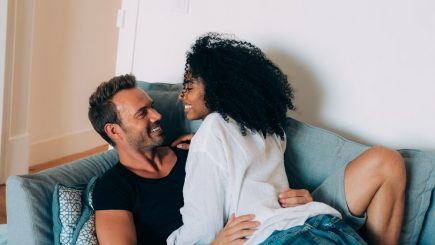 interracial couple cuddling on a couch