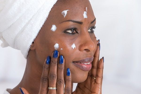 older black woman applying facial essence